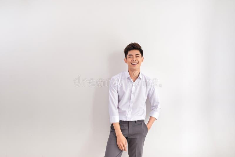 St?ende av det lyckliga anseendet f?r ung man mot vit bakgrund arkivfoton