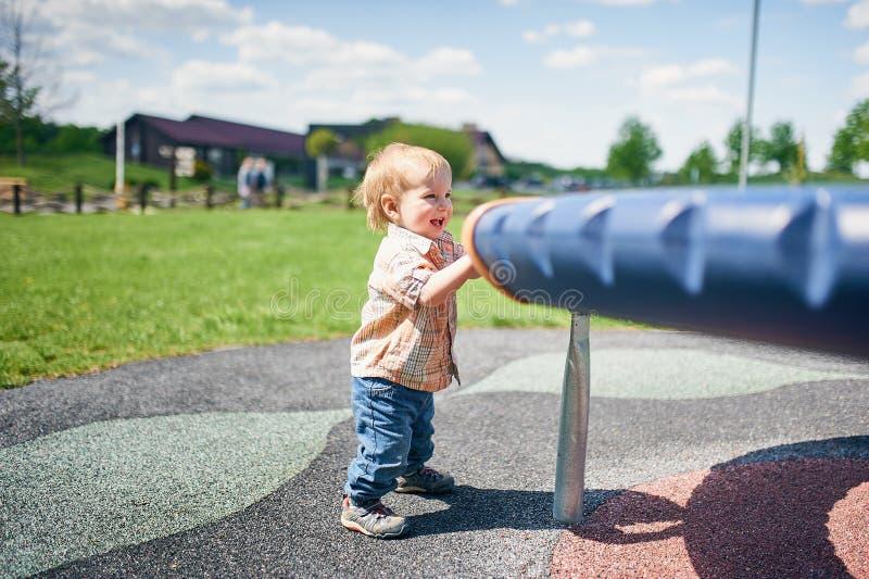 St?ende av det lyckliga le lilla litet barnpojkeanseendet n?ra gungorna p? lekplatsen utanf?r p? sommardag royaltyfri foto