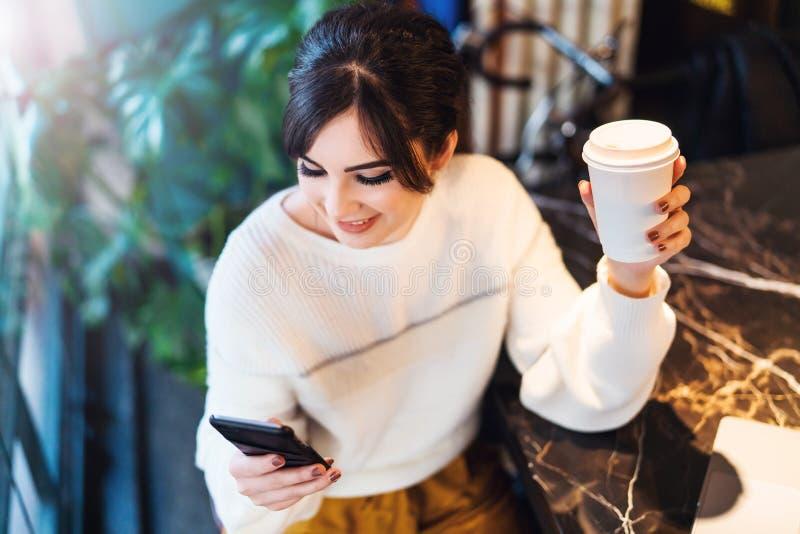 St?ende av det sittande kaf?t f?r flicka, genom att anv?nda smartphonen Den unga kvinnan l?ser textmeddelandet p? telefonen, meda arkivfoto