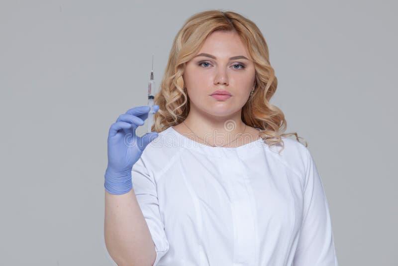St?ende av doktorn eller sjuksk?terskan f?r ung kvinna i skyddande handskar som rymmer en injektion royaltyfria foton