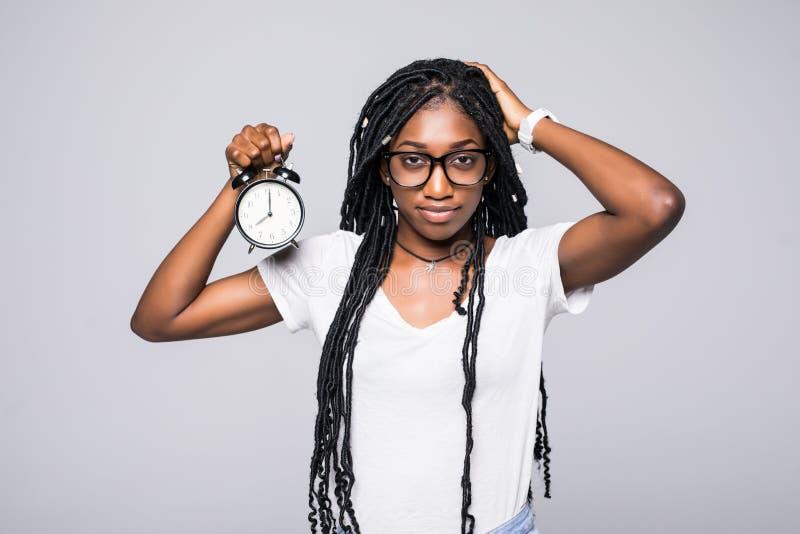 St?ende av en chockad ung afro amerikansk kvinnainnehavringklocka som isoleras ?ver gr? bakgrund royaltyfria bilder