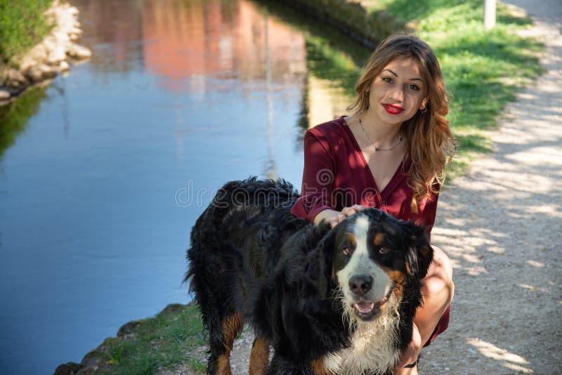 St?ende av en h?rlig flicka som squatting med hennes hund vid en str?m royaltyfri foto