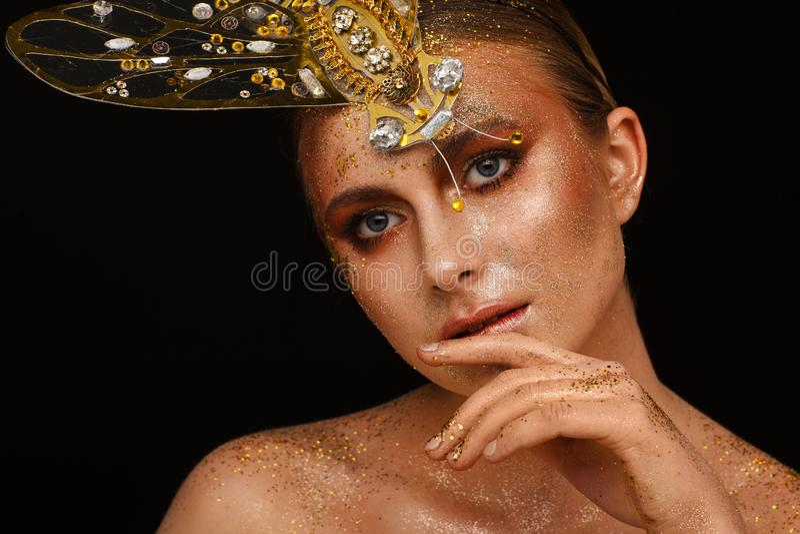 St?ende av en h?rlig kvinna med uttrycksfullt id?rikt smink i brons och med en garnering p? hennes huvud arkivfoto
