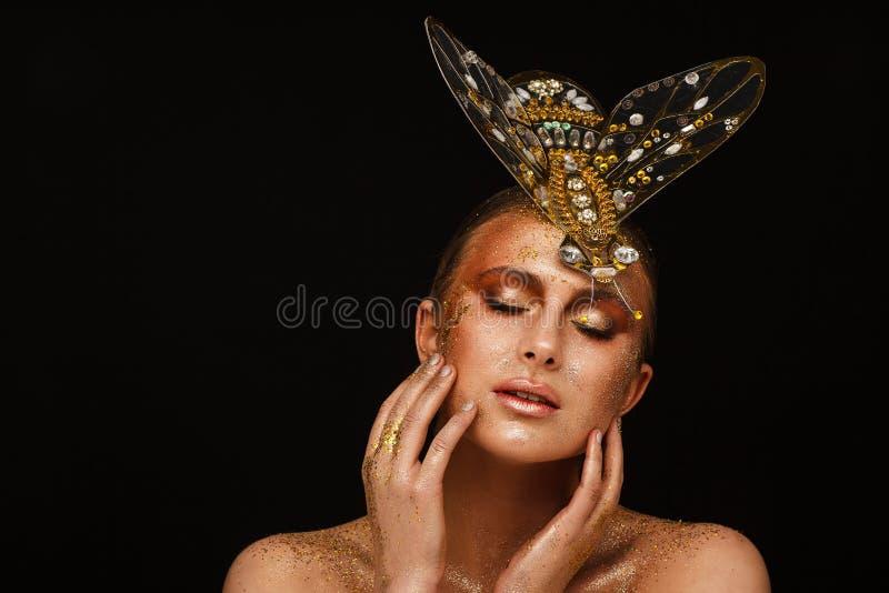 St?ende av en h?rlig kvinna med uttrycksfullt id?rikt smink i brons och med en garnering p? hennes huvud fotografering för bildbyråer