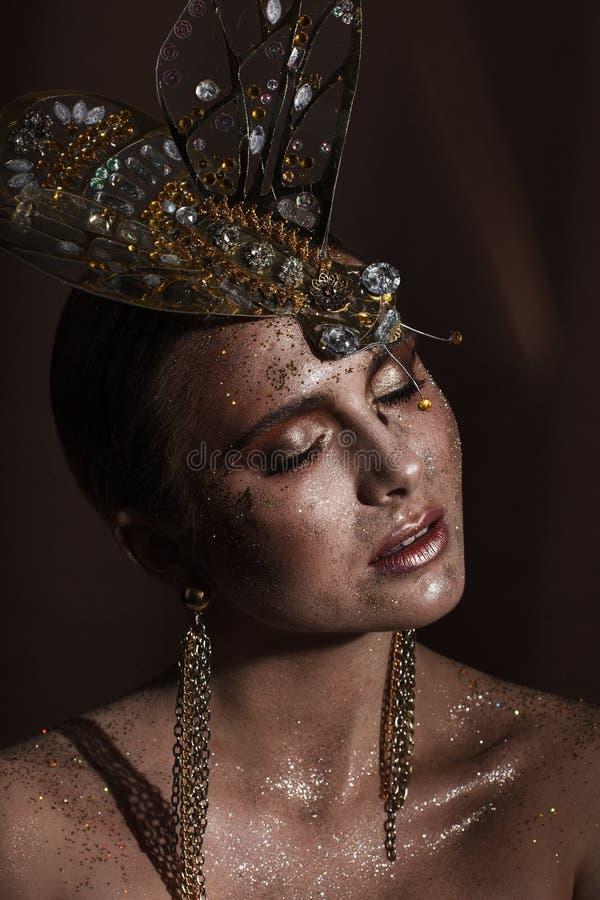 St?ende av en h?rlig kvinna med uttrycksfullt id?rikt smink i brons och med en garnering p? hennes huvud royaltyfri bild
