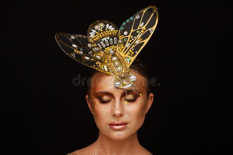 St?ende av en h?rlig kvinna med uttrycksfullt id?rikt smink i brons och med en garnering p? hennes huvud arkivbilder