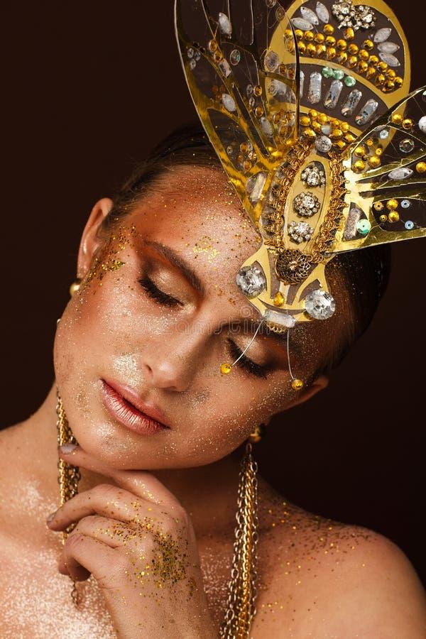 St?ende av en h?rlig kvinna med uttrycksfullt id?rikt smink i brons och med en garnering p? hennes huvud royaltyfria foton