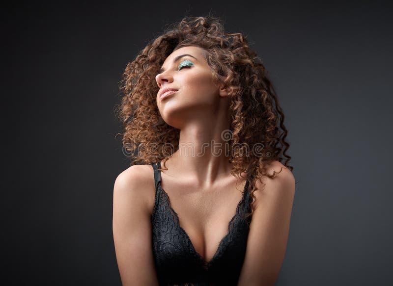 St?ende av en h?rlig kvinnlig modemodell med lockigt h?r royaltyfri foto
