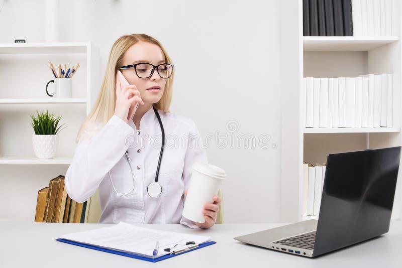 St?ende av en h?rlig le kvinnadoktor, medan tala p? smartphonen och att avsluta en medicinsk information arkivbild