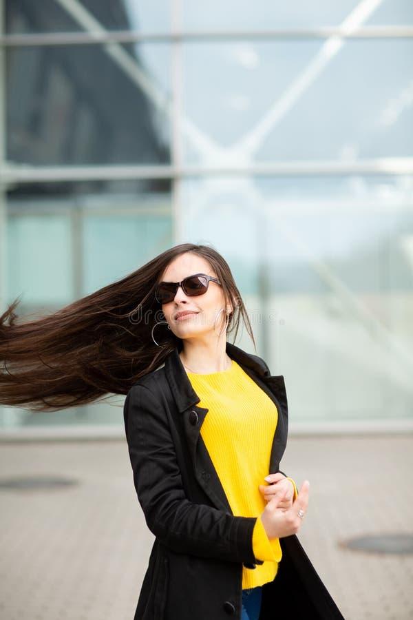 St?ende av en h?rlig trendig stilfull kvinna i ljus gul tr?ja Gatastilskytte royaltyfri fotografi