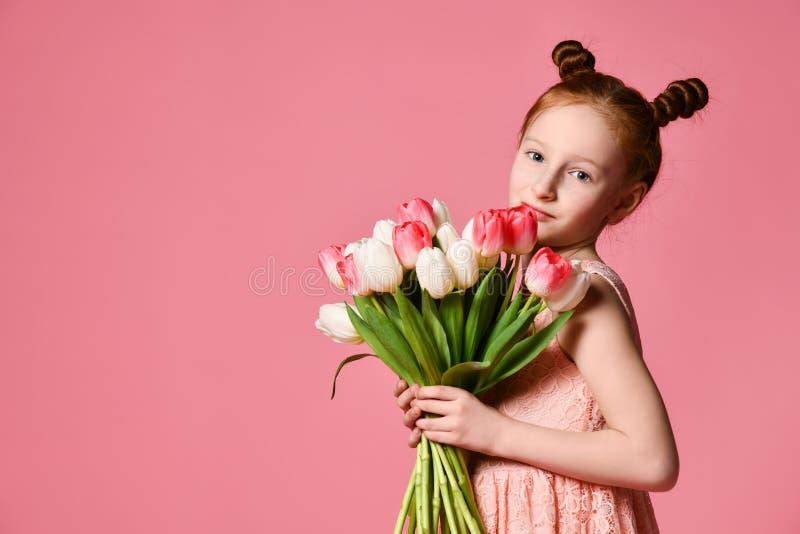 St?ende av en h?rlig ung flicka i kl?nningen som rymmer den stora buketten av iriers och tulpan som isoleras ?ver rosa bakgrund arkivfoto