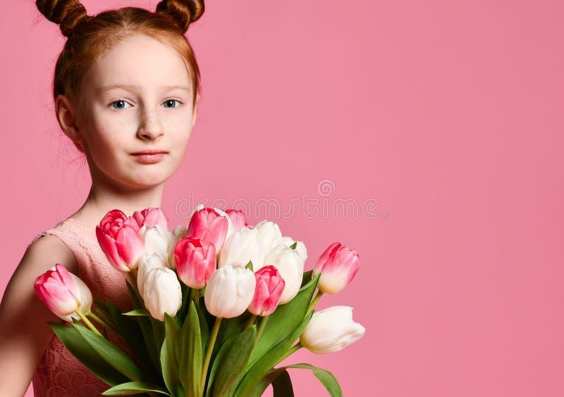 St?ende av en h?rlig ung flicka i kl?nningen som rymmer den stora buketten av iriers och tulpan som isoleras ?ver rosa bakgrund arkivbilder