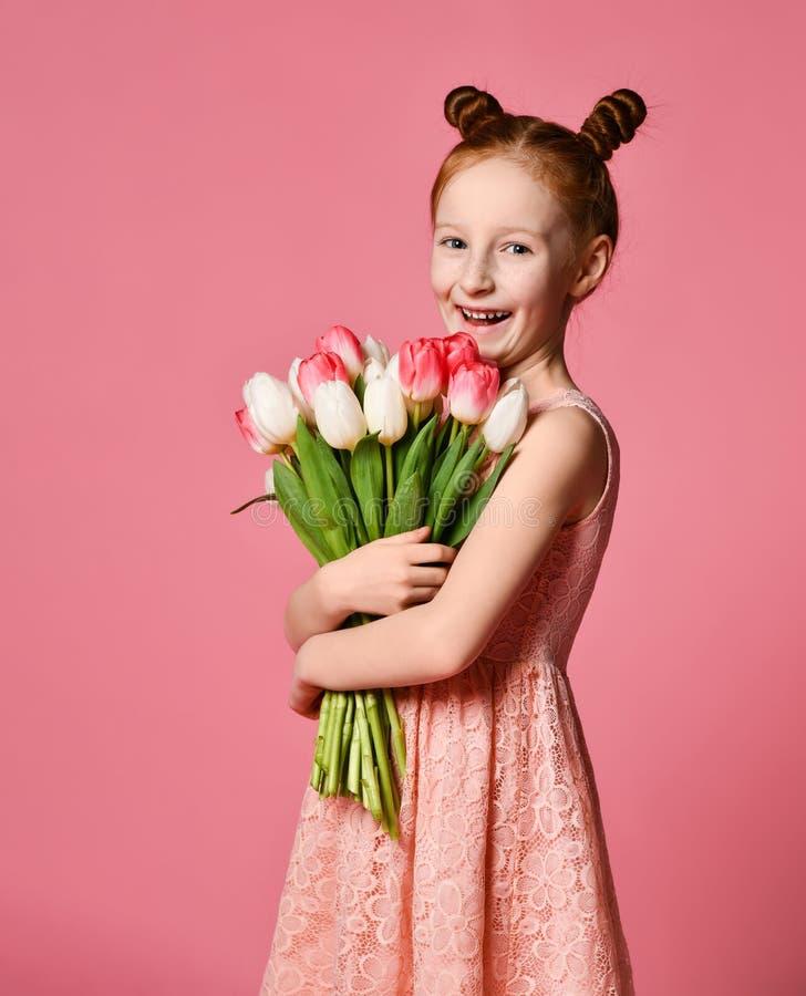 St?ende av en h?rlig ung flicka i kl?nningen som rymmer den stora buketten av iriers och tulpan som isoleras ?ver rosa bakgrund royaltyfri bild