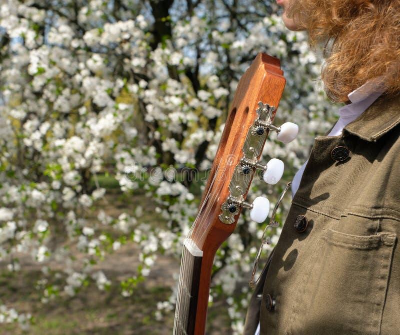 St?ende av en h?rlig ung kvinna med en gitarr arkivfoton