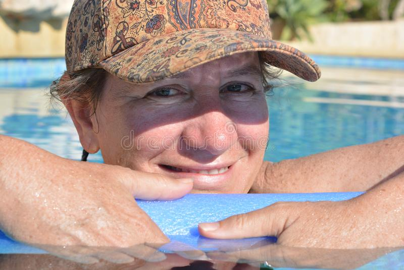St?ende av en kvinna i simbass?ng arkivfoto