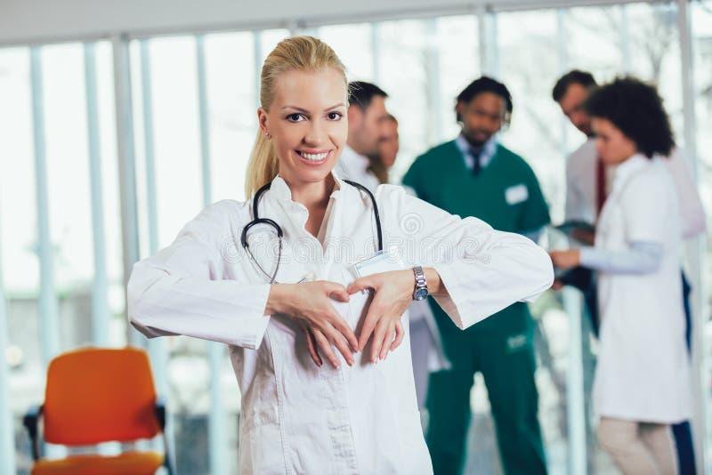 St?ende av en kvinnlig doktor som visar hj?rtagest med h?nder arkivbild