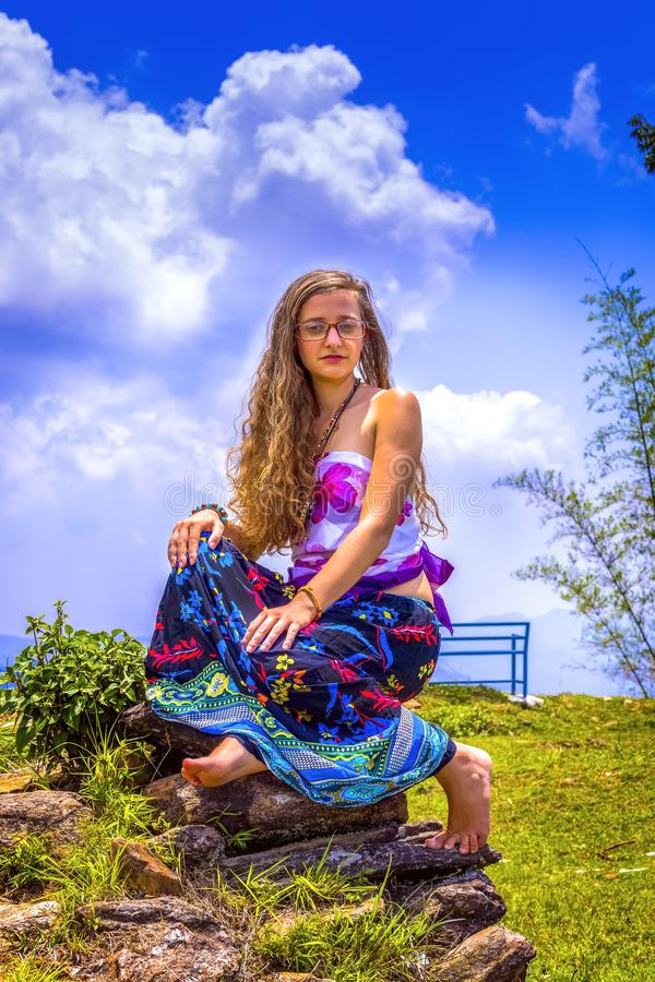 St?ende av en lycklig ung flicka och en kl?dd blom- maxi kjol med ?verkanten arkivbild