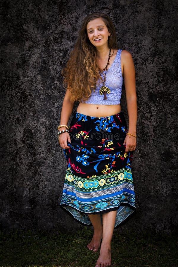 St?ende av en lycklig ung flicka och en kl?dd blom- maxi kjol med ?verkanten arkivbilder