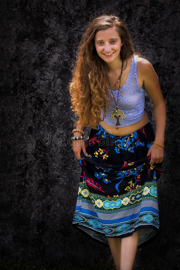 St?ende av en lycklig ung flicka och en kl?dd blom- maxi kjol med ?verkanten fotografering för bildbyråer