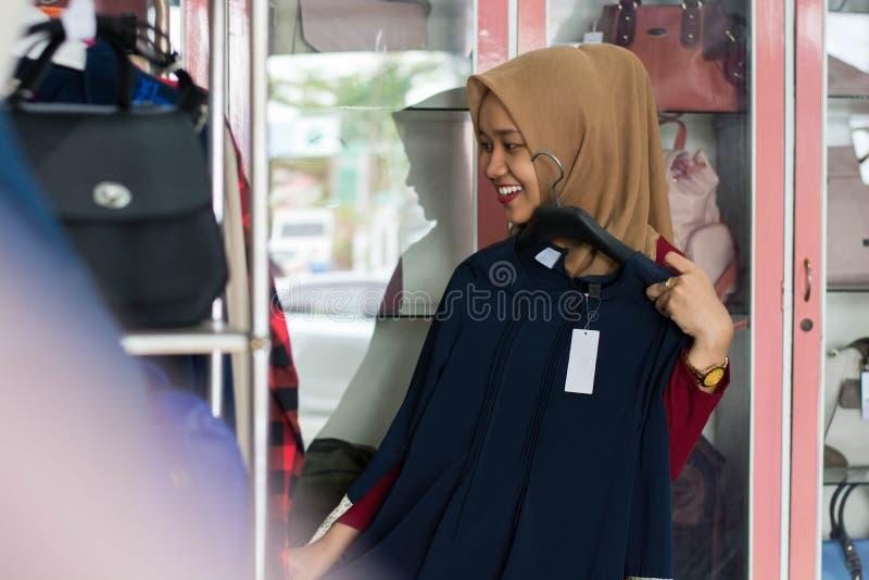 St?ende av en muslim kvinnashopping f?r attraktiv ung asiat i en modestrore fotografering för bildbyråer