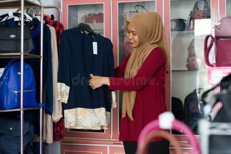 St?ende av en muslim kvinnashopping f?r attraktiv ung asiat i en modestrore arkivbild