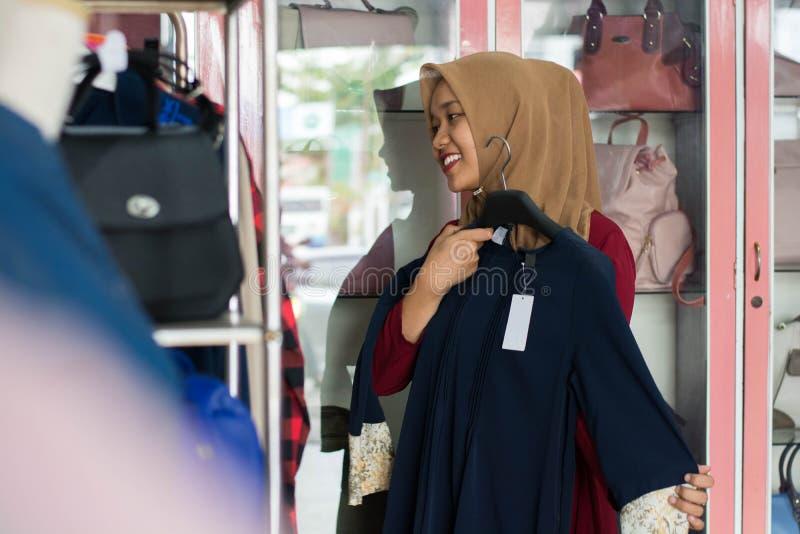 St?ende av en muslim kvinnashopping f?r attraktiv ung asiat i en modestrore royaltyfri foto