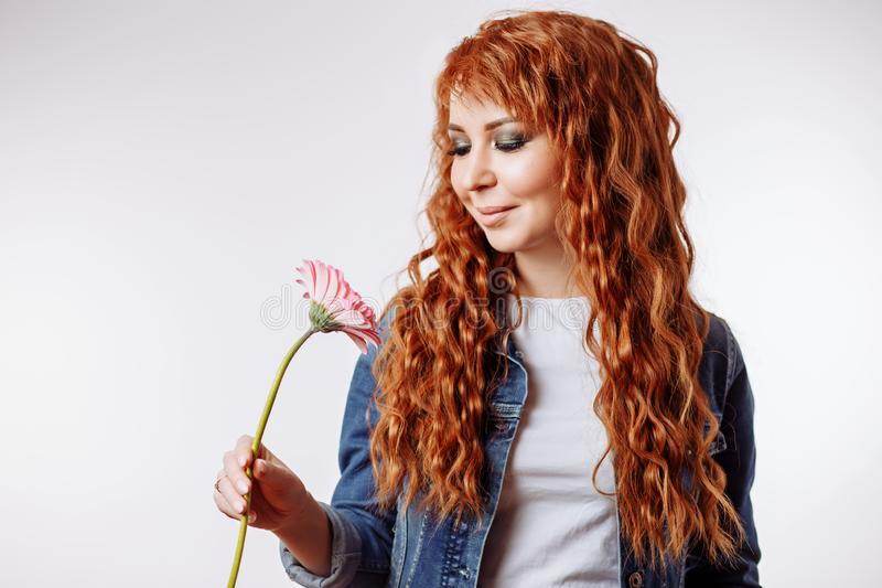 St?ende av en n?tt caucasian kvinna som ler och rymmer blomman p? vit bakgrund royaltyfria bilder