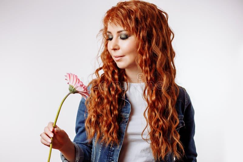 St?ende av en n?tt caucasian kvinna som ler och rymmer blomman p? vit bakgrund royaltyfri bild