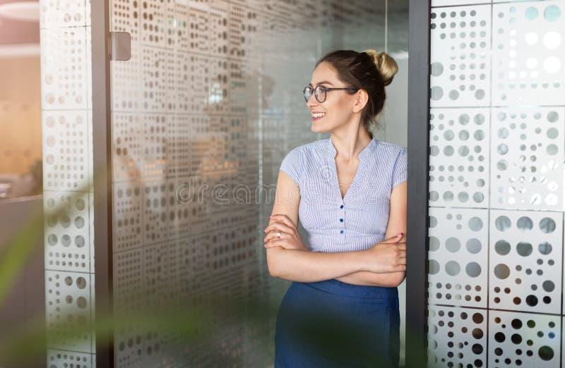 St?ende av en ung aff?rskvinna i ett kontor royaltyfri foto
