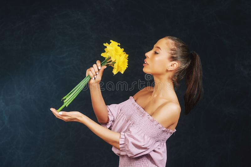 St?ende av en ung h?rlig flicka med blommor i studion arkivfoto