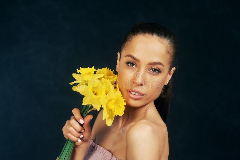 St?ende av en ung h?rlig flicka med blommor i studion fotografering för bildbyråer