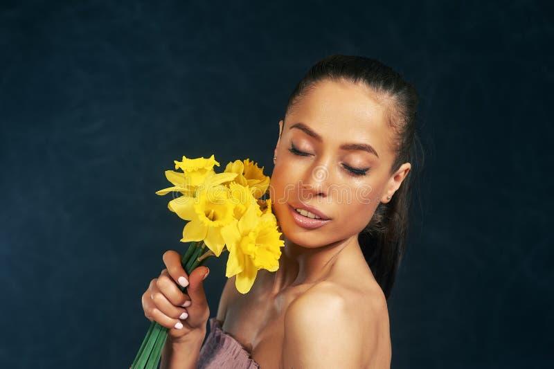 St?ende av en ung h?rlig flicka med blommor i studion arkivbild