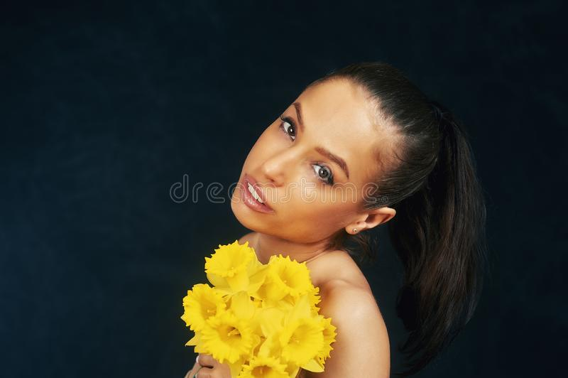 St?ende av en ung h?rlig flicka med blommor i studion arkivfoton