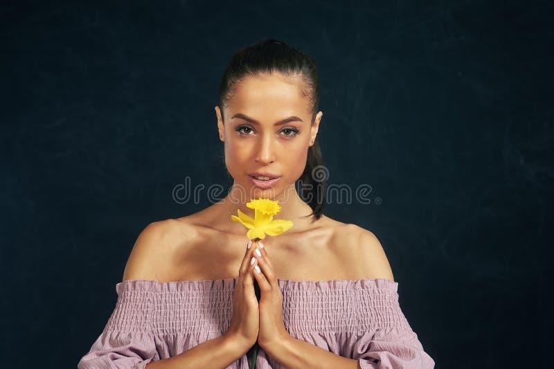 St?ende av en ung h?rlig flicka med blommor i studion arkivbilder