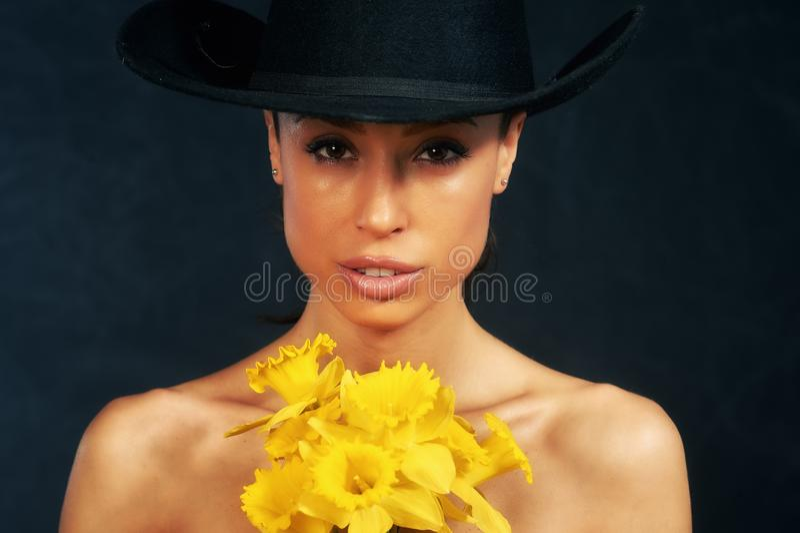 St?ende av en ung h?rlig flicka med blommor i studion royaltyfri foto
