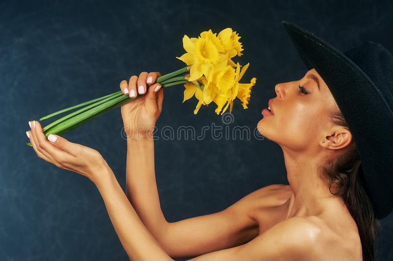 St?ende av en ung h?rlig flicka med blommor i studion royaltyfri fotografi