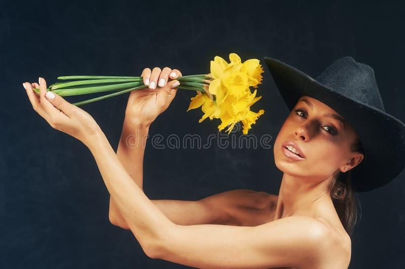 St?ende av en ung h?rlig flicka med blommor i studion royaltyfria bilder