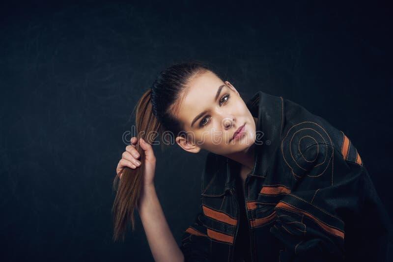 St?ende av en ung h?rlig flicka p? en m?rk bakgrund arkivbild