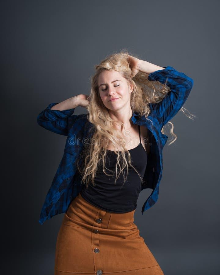 St?ende av en ung kvinna flickan lyssnar och tycker om musik livsstilfolkbegrepp royaltyfri foto