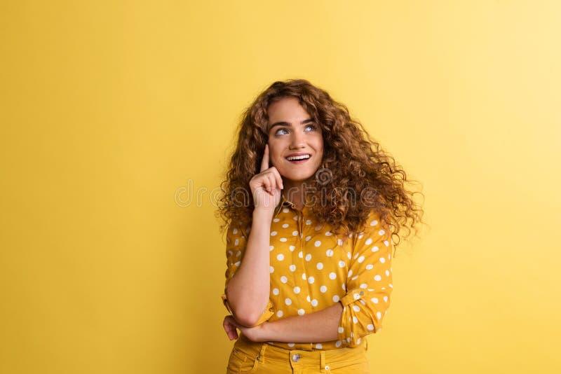 St?ende av en ung kvinna i en studio p? en gul bakgrund royaltyfri foto
