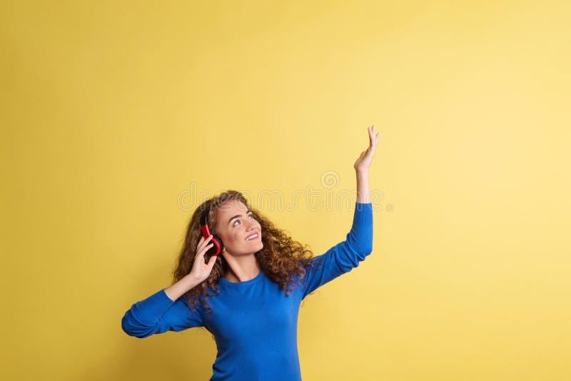 St?ende av en ung kvinna med h?rlurar i en studio p? en gul bakgrund royaltyfria foton