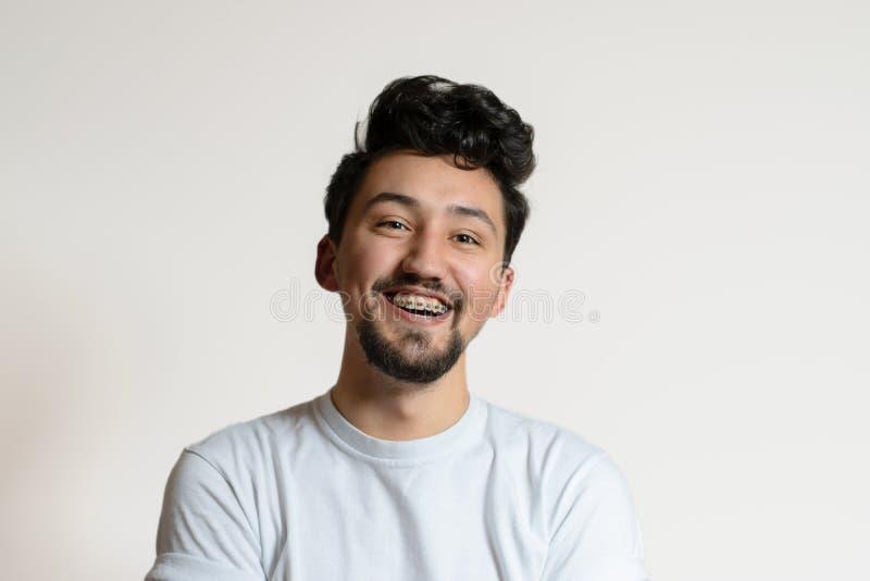 St?ende av en ung man med h?nglsen som ler och skrattar En lycklig ung man med h?nglsen p? en vit bakgrund arkivfoton
