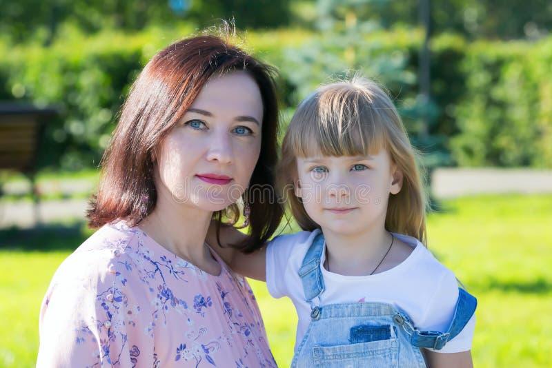 St?ende av en ung moder med en behandla som ett barn royaltyfri bild