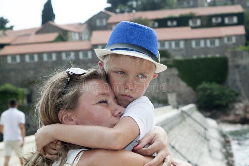 st?ende av en ung moder som kramar hennes barn p? semester p? arkivbild