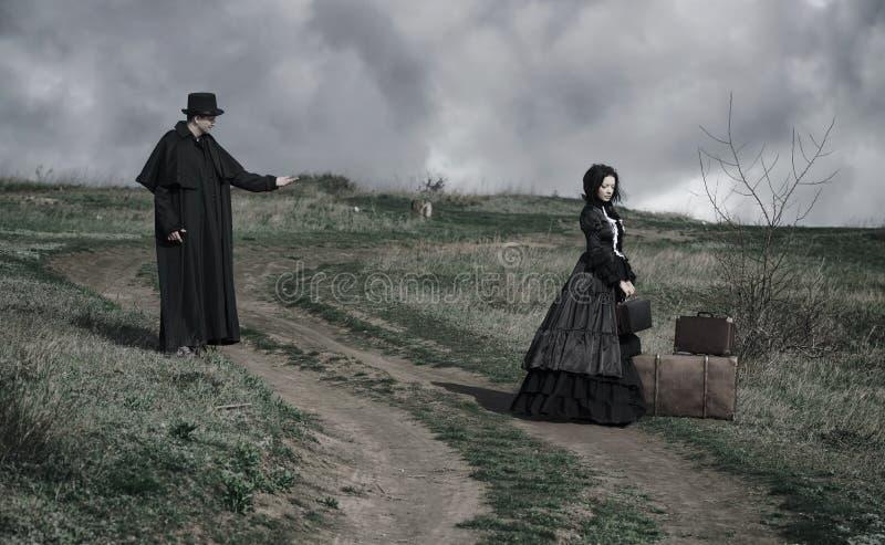 St?ende av en victorian dam i svart sammantr?de p? v?gen med hennes n?rliggande bagage- och gentlemananseende royaltyfria bilder