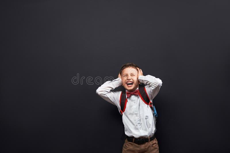 St?ende av ett emotionellt barn pojkeskolpojkeskrin plaskar ut negativa sinnesrörelser begreppet av studenten ropar ingen lust ti arkivbilder