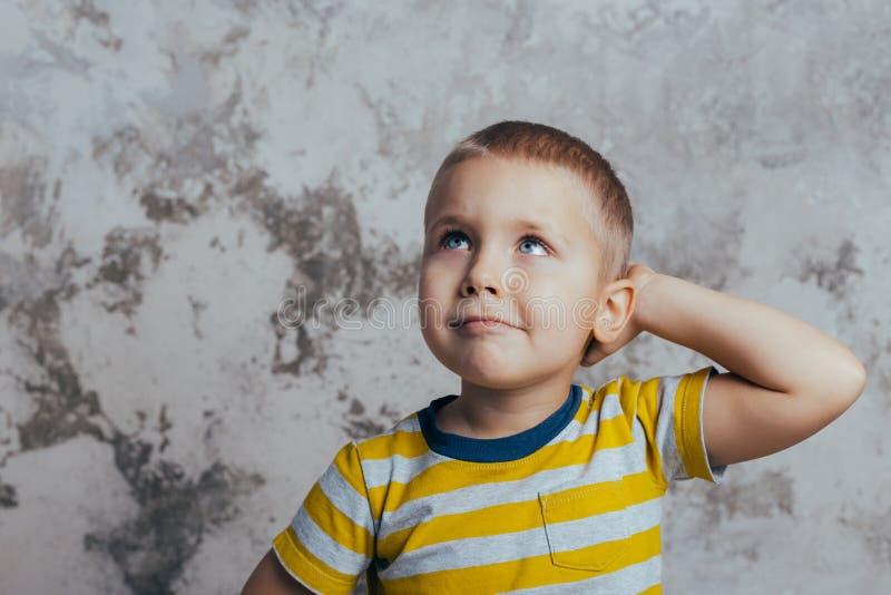 St?ende av ett fundersamt gulligt litet barn med handen som trycker p? framsidan arkivfoto