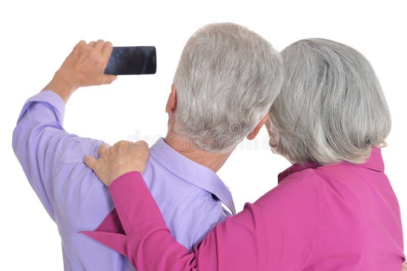 St?ende av ett lyckligt h?gt par som tar selfiefotoet p? vit bakgrund royaltyfri bild
