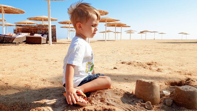 St?ende av gulliga 3 ?r gammal litet barnpojke som sitter p? den sandiga stranden och spelar med leksaker och den byggande sandsl arkivfoton