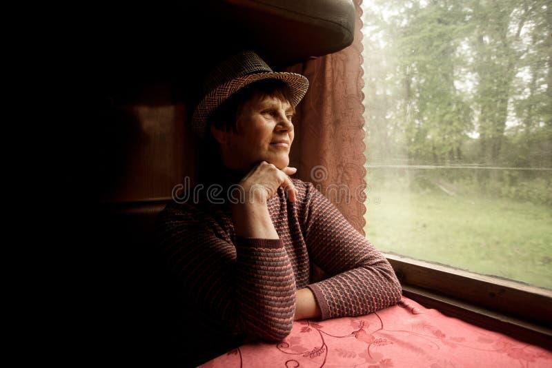 St?ende av h?rliga 60 ?r gammal kvinna i hatten som sitter i drev royaltyfri foto